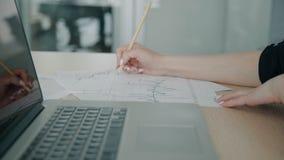 Chiuda su di lavorare anatytic finanziario femminile ai grafici di carta nel suo ufficio archivi video