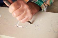 Chiuda su di Mason At Work On Carving di pietra in studio immagini stock libere da diritti