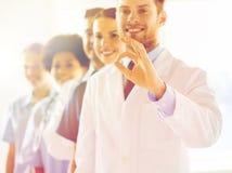 Chiuda su di medici che mostrano il segno giusto all'ospedale Fotografia Stock Libera da Diritti