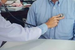 Chiuda su di medico che ascolta il battito cardiaco paziente con lo stethosco Immagine Stock Libera da Diritti