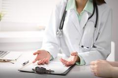 Chiuda su di medico e del paziente che si siedono allo scrittorio vicino alla finestra in ospedale Immagine Stock