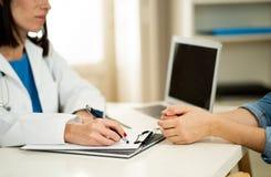 Chiuda su di medico e del paziente della donna che hanno consultazione nella stanza di ospedale fotografia stock