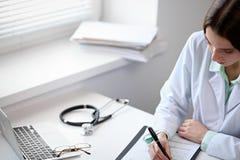 Chiuda su di medico femminile sconosciuto che si siede alla tavola vicino alla finestra in ospedale Immagine Stock