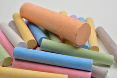 Chiuda su di molti pezzi colorati del gesso sopra su un backgrou bianco Immagine Stock