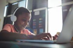 Chiuda su di musica d'ascolto del ragazzo mentre per mezzo del computer portatile Fotografia Stock