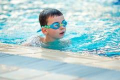 Chiuda su di nuoto del ragazzo del bambino nello stagno Fotografia Stock Libera da Diritti
