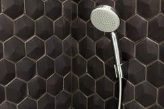 Chiuda su di nuova testa di doccia della pioggia nel bagno contro un fondo delle mattonelle nere fotografie stock libere da diritti