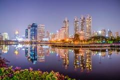 Chiuda su di paesaggio urbano di notte al parco di Benchakitti, costruzione moderna di Bangkok, Tailandia, le foto della riflessi immagini stock