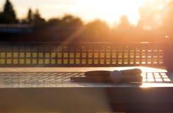 Chiuda su di palla da ping-pong con le racchette di tennis sulla tavola di pietra alle luci soleggiate, attrezzatura del tennis p Fotografie Stock