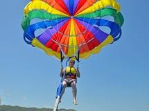 Chiuda su di parasailing della donna in chiaro cielo blu Fotografie Stock Libere da Diritti