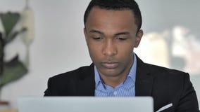 Chiuda su di pensiero dell'uomo d'affari afroamericano casuale Working sul computer portatile, vista frontale video d archivio