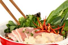 Chiuda su di Pho con la minestra affettata della carne di maiale su fondo bianco Fotografia Stock