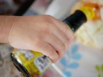 Chiuda su di piccola mano del ` s del bambino che tiene una bottiglia della salsa del fagiolo della soia immagini stock