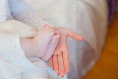 Chiuda su di piccoli piedi del bambino con la mano della madre Fotografia Stock Libera da Diritti