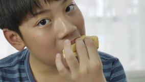 Chiuda su di poco ragazzo asiatico godono di di mangiare il gelato a casa 4K archivi video