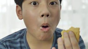 Chiuda su di poco ragazzo asiatico godono di di mangiare il gelato a casa 4K stock footage