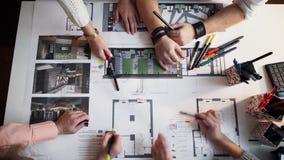 Chiuda su di quattro architetti che discutono insieme il piano al timalapse dello scrittorio stock footage