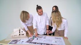 Chiuda su di quattro architetti che discutono insieme il piano allo scrittorio con i modelli stock footage
