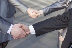 Chiuda su di quattro genti di affari che stringono le mani Fotografie Stock