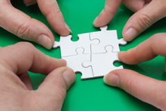 Quattro genti con il puzzle Immagini Stock Libere da Diritti