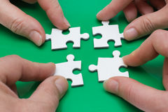 Quattro genti con il puzzle Fotografia Stock Libera da Diritti