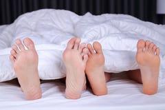 Chiuda su di quattro piedi a letto immagini stock libere da diritti