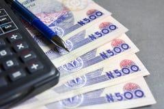 Chiuda su di riso con la penna nigeriana ed il calcolatore di spirito di cinquecento note di naira immagini stock libere da diritti