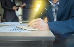 Chiuda su di scrittura della mano dell'uomo di affari sulla carta del taccuino con il bus immagine stock libera da diritti