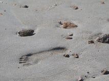 Chiuda su di singola stampa del piede sulla sabbia con le pietre uno spazio della copia fotografia stock libera da diritti