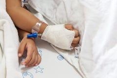 Chiuda su di sonno malato dei bambini della mano sul letto Fotografia Stock