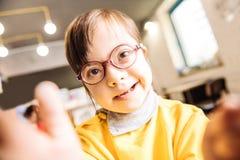Chiuda su di sorridere d'uso di vetro del bambino soleggiato dagli occhi scuri piacevole immagine stock