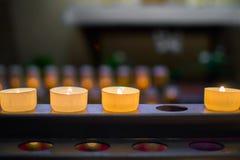 Chiuda su di tre candele brucianti in una fila senza una candela, con profondit? di campo bassa incompleto immagine stock libera da diritti