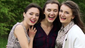 Chiuda su di tre ragazze nell'abbraccio che sorridono e che esaminano una macchina fotografica lentamente archivi video