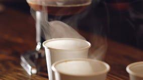 Chiuda su di tre tazze di caffè delizioso sulla tavola di legno video d archivio