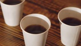 Chiuda su di tre tazze di caffè delizioso sulla tavola di legno archivi video