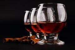 Chiuda su di tre vetri del calice in una fila con il cognac, rum o brandy scuro e bastoni di cannella sparsi su un fondo nero con fotografie stock libere da diritti