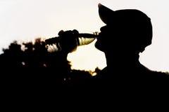 Chiuda su di un'acqua potabile dell'uomo da una bottiglia dopo l'esercizio fotografia stock libera da diritti