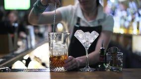Chiuda su di un barista della donna che mescola il ghiaccio in una brocca stock footage
