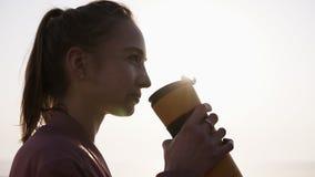 Chiuda su di un bello, sognando la giovane donna La ragazza sta godendo del momento Bevande da una tazza di sport respirazione Il stock footage