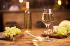 Chiuda su di un bicchiere di vino accanto ad una ciotola di miele dorato saporito su una tavola di legno in un pub d'annata fotografia stock