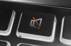 Chiuda su di un bottone nero del muto del volume di un telecomando nero con la lampadina immagine stock