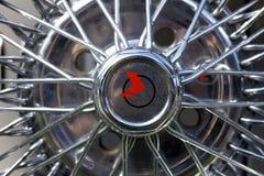 Chiuda su di un cappuccio di hub della ruota del raggio del cromo su un'automobile classica fotografie stock libere da diritti