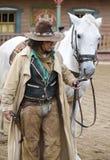Chiuda in su di un cowboy che si leva in piedi vicino al suo cavallo Fotografie Stock Libere da Diritti
