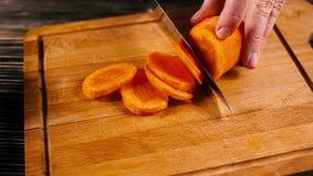 Chiuda su di un cuoco unico che taglia con attenzione alcune carote video d archivio