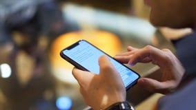 Chiuda su di un dispositivo di tenuta dell'uomo e di lettura del testo sullo schermo, concetto moderno delle tecnologie azione Un immagini stock libere da diritti