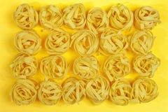Chiuda su di un fettuccine italiano asciutto crudo della pasta su giallo luminoso Fotografia Stock Libera da Diritti