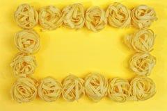 Chiuda su di un fettuccine italiano asciutto crudo della pasta su giallo luminoso Fotografia Stock
