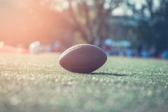 Chiuda su di un football americano sul campo, giocatori nelle sedere immagine stock libera da diritti