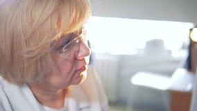 Chiuda su di un fronte di un medico femminile biondo archivi video