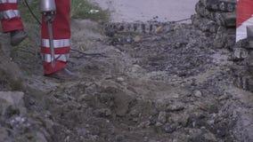 Chiuda su di un lavoratore in pantaloni rossi facendo uso di un martello pneumatico sulla terra archivi video